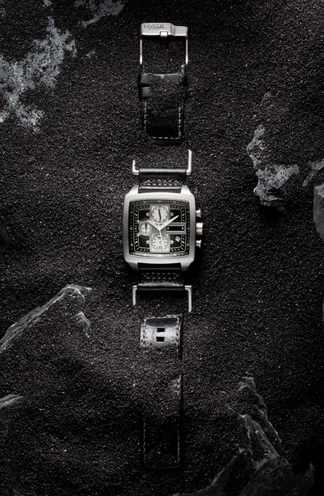 Fossil watch on black sand with stones
